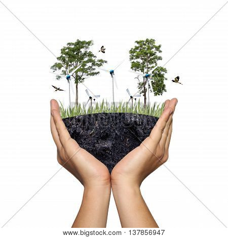 A tree and wind turbine on ground in the hands of menPhoto montage showing in concept of natural energy for reduce global warmingBeautiful world with our hands.