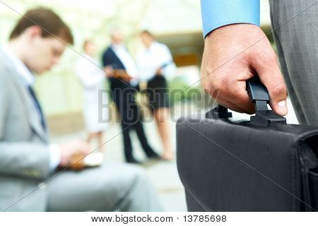 Close-up of businessman hand holding briefcase in working environment