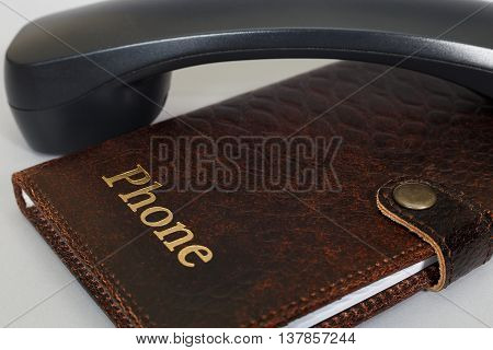 Black handset and notebook with the words