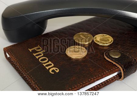 Brown notebook with the inscription '' Phone '', black handset and coins