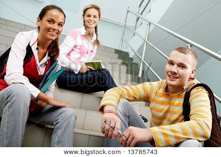 Portrait of three teens sitting on stairs and looking at camera in college