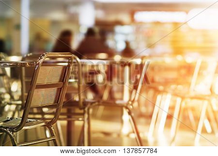 Horizontal empty cafe left aligned chair bokeh with light leak background