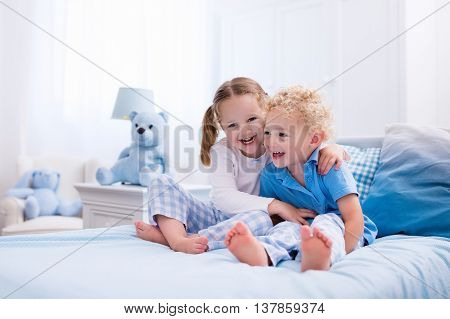 Happy kids playing in white bedroom. Little boy and girl brother and sister play on the bed wearing pajamas. Nursery interior for children. Nightwear and bedding for baby and toddler. Family at home.