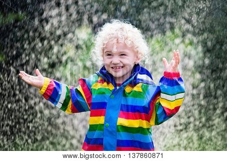 Little blond curly boy in a waterproof jacket in rainbow color playing in the rain. Kids having fun outdoors in autumn shower.