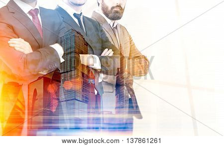 Teamwork concept with businesspeople crossing arms on city background with sunlight. Double exposure