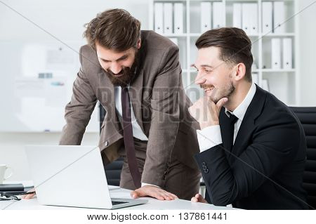 Two attractive cheerful businessmen working on project in modern bright office. Teamwork concept
