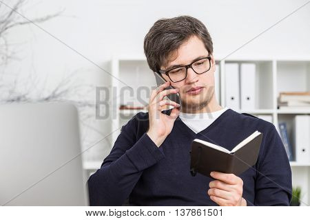 Attractive young businessman talking on phone and checking schedule in organizer at his workplace