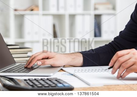 Side view of accountant's hands doing paperwork on cork desktop with calculator and laptop keyboard on office interior background