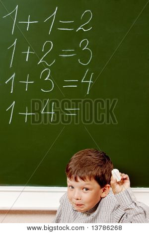 Portrait of curious schoolchild standing at blackboard with written sums on it and looking at camera