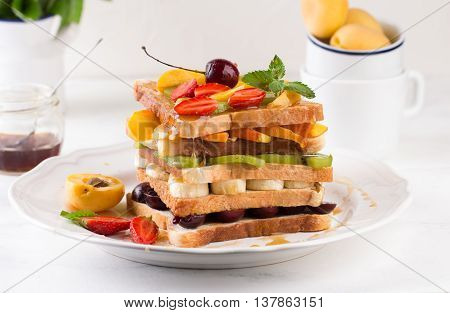 Stack of French toast with fresh strawberries, peaches, cherry, kiwi and banana, poured with maple syrup