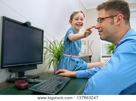 Father and daughter working at home with personal computer.