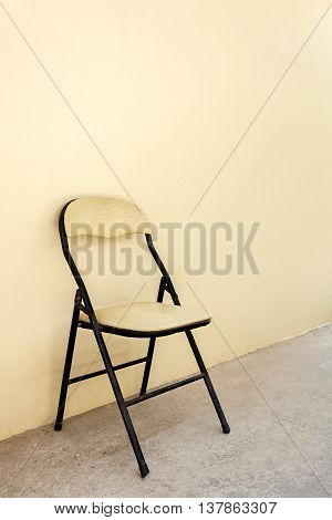 Old Chair On Cement Floor With Cream-colored Wall
