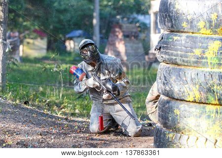 Man with sniper paintball riffle sitting in ambush