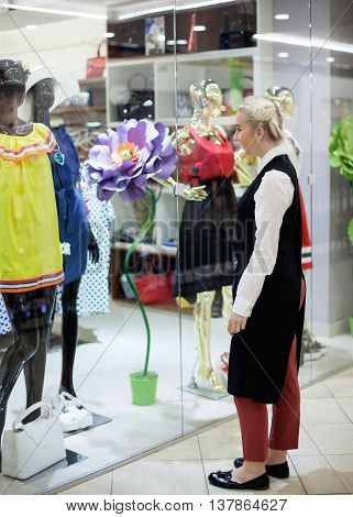 Young woman standing against shopfront and looking at clothes