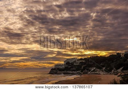 Dramatic cloudscape at sunset. Scenic view of sunset beach. Salou Spain. Summer vacations concept. Horizontal.