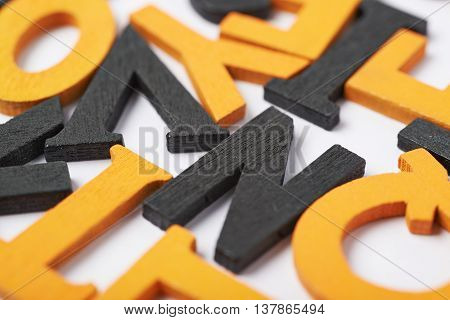 White surface covered with the multiple colorful black and orange painted wooden letters as a Halloween backdrop composition