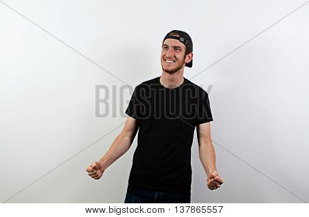 Joyful Happy Smiling Young Adult Male in Dark T-Shirt and Baseball Hat Worn Backwards
