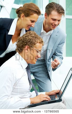 Image of businesspeople looking at laptop that male holds at meeting