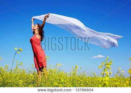 Image of happy woman holding a white fabric in the yellow meadow