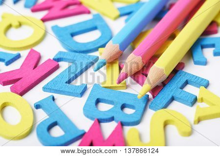 White surface covered with the multiple colorful painted wooden letters with the drawing pencils over it, composition as a backdrop composition
