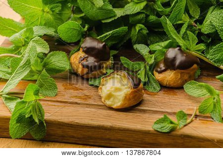 Three eclairs lying on wooden board decorated with green mint leaves
