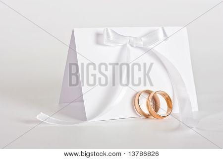 Hochzeits-Ringe und laden mit weißen Bogen