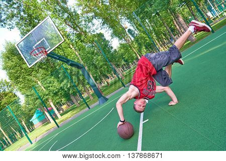 B-boy doing stunt trick on basketball playground with ball