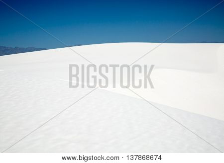 The view of a white gypsum sand dune with a mountain in the background at White Sands National Monument.