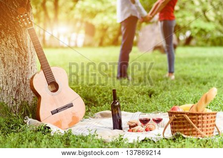 Close up of guitar with wine and food on blanket in park. Loving couple is standing and holding hands on background