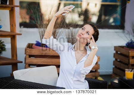 Business woman taking selfie with orange fresh juice at outdoors cafe during the lunch.