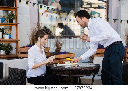 Waiter server at table working reading menu specials list for group of people.