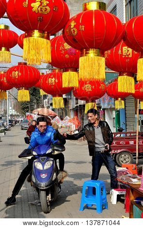 Jun Le China - January 25 2014: Young men hanging out under a canopy of bright red lantern Chinese Lunar New Year decorations