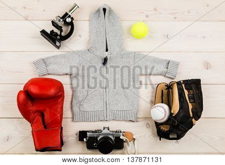 Future occupation concept. Top view of grey baby boy hoodie surrounded with boxing glove baseball equipment tennis ball microscope and photo camera on light wooden table