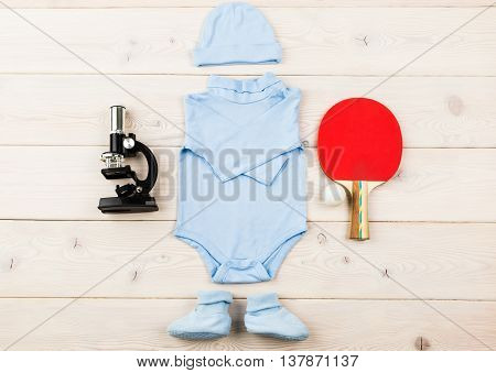 Future occupation concept. Top view of blue baby boy bodysuit socks and hat surrounded with microscope and table tennis equipment on light wooden surface