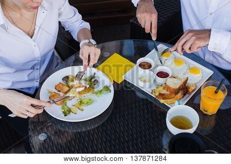 Closeup of business people hands, male and female having breakfast at outdoors cafe. Meals with salad, omelette, bacon
