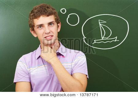 Portrait of smart lad by the blackboard thinking of sailing
