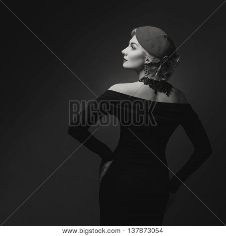 Beautiful lady in beret. Film noir retro style. Over black background. Monochrome.