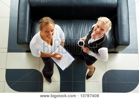 Above angle of two friendly employees standing by sofa and looking at camera