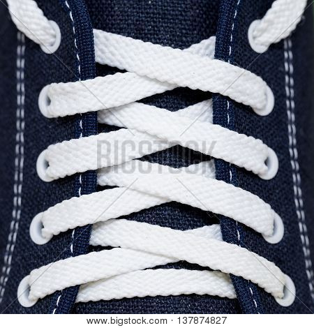 Lacing with white laces at the blue cloth sports Shoe with stitches of white thread
