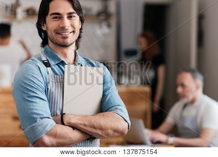 Handsome diner. Cheerful and positive male cafe worker holding a menu while standing and happily smiling at a camera with some people in a background