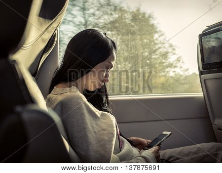 Woman sitting at train and looking to mobil phone.
