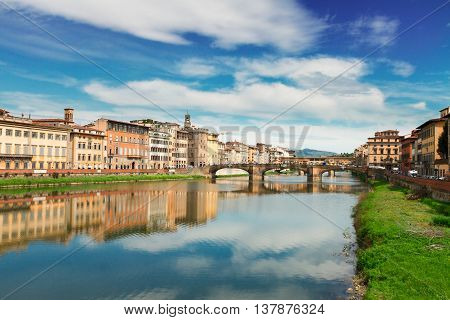 old town, bridges and river Arno reflecting in water at summer day, Florence, Italy