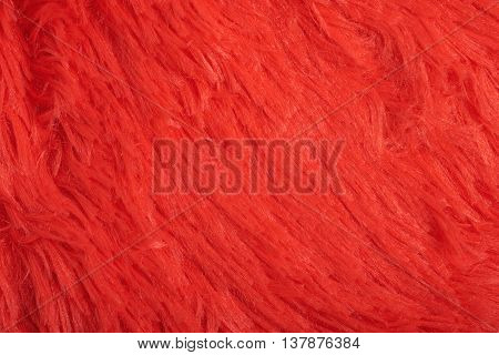 Artificial red fur cloth fragment as a background texture composition