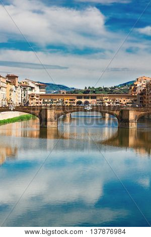 Ponte Santa Trinita bridge over the Arno River with cloudy sky and reflections, Florence, Italy