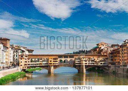 famous bridge Ponte Vecchio over waters of river Arno with cloudy sky, Florence, Italy