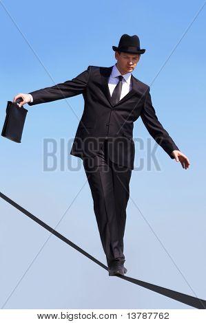Foto von erfahrenen Geschäftsmann hinunter Band oder Seil mit blauen Himmel im Hintergrund