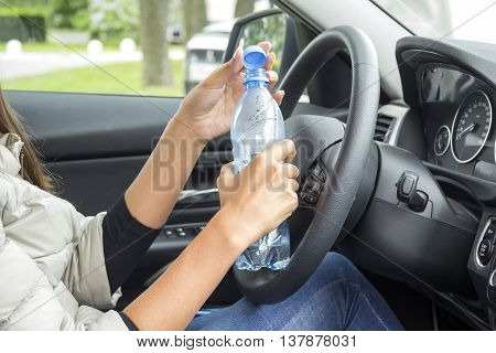 the girl in the cabin of the car holding a bottle of water