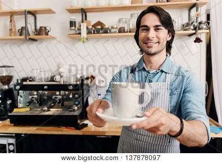 Time to drink coffee. Happy and cheerful male barista holding a cup of coffee at coffee shop