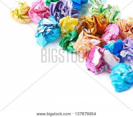 Pile of colorful crumbled origame paper sheet balls isolated over the white background, close-up crop fragment