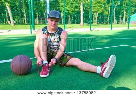 Man tying shoelaces relying on basketball ball on green playground